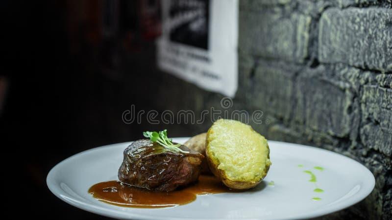 Batatas cozidas enchidas com carne e molho de assado grelhados e verdes na tabela na barra Almoço delicioso maravilhoso fotografia de stock