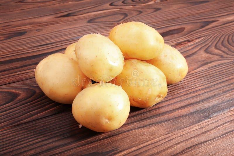 Batatas cruas, frescas e crus em um fundo de madeira do marrom escuro Produto-vegetais frescos de vegetables Alimento fresco vege foto de stock