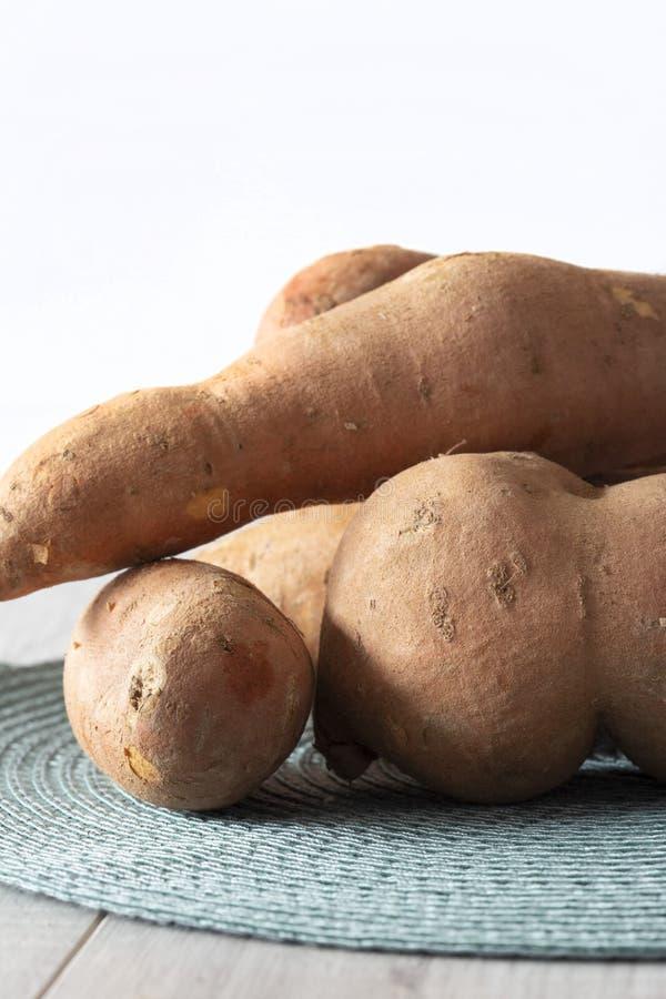 Batatas doces empilhadas em uma esteira de lugar verde em uma superf?cie de madeira cinzenta imagem de stock