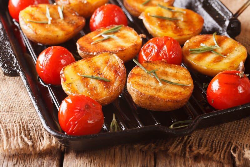 Batatas e tomates Roasted com alecrins perto acima em uma grade foto de stock royalty free