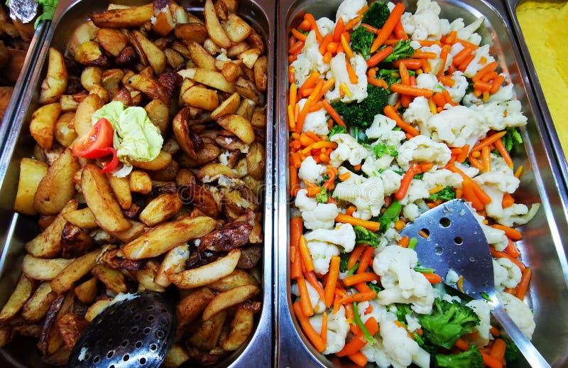 Batatas e vegetais do camponês em bandejas de aço inoxidável fotografia de stock royalty free