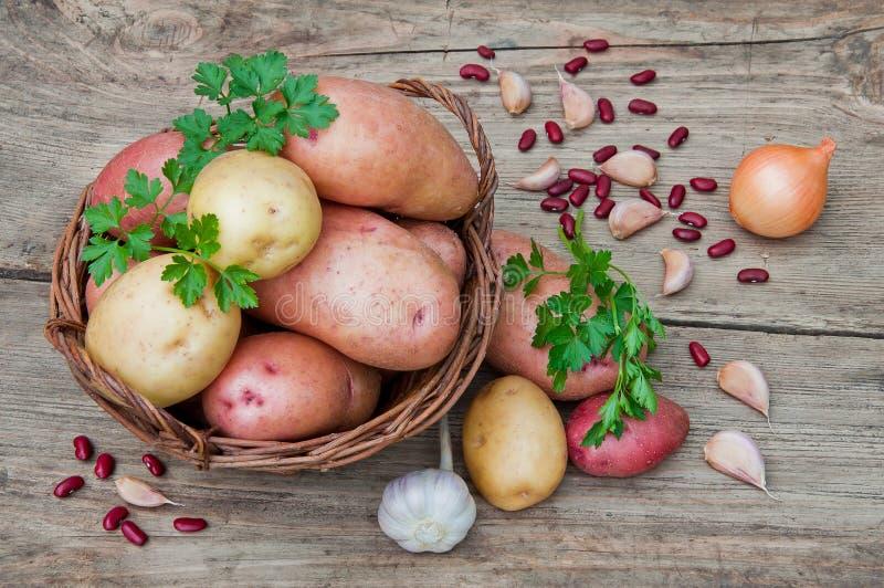 Batatas em uma cesta de vime em uma tabela de madeira no estilo rústico foto de stock royalty free