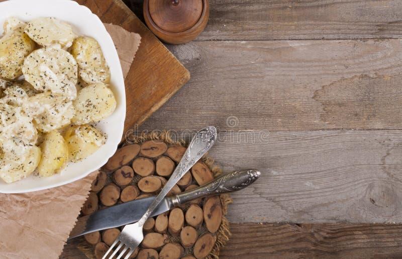 Batatas fervidas em uma placa branca alimento diet?tico Fundo de madeira, cutelaria de madeira Vista de acima foto de stock