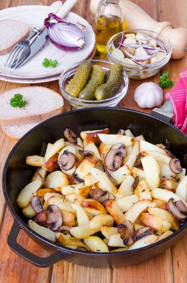 Batatas fritadas com cogumelos em uma bandeja em um fundo de madeira fotografia de stock royalty free