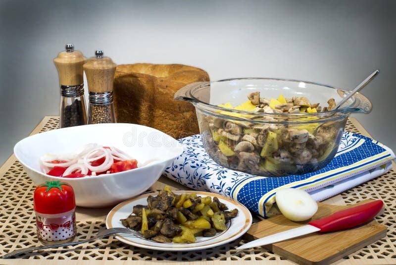 Batatas fritadas com cogumelos, salada de tomates frescos e pão caseiro imagem de stock
