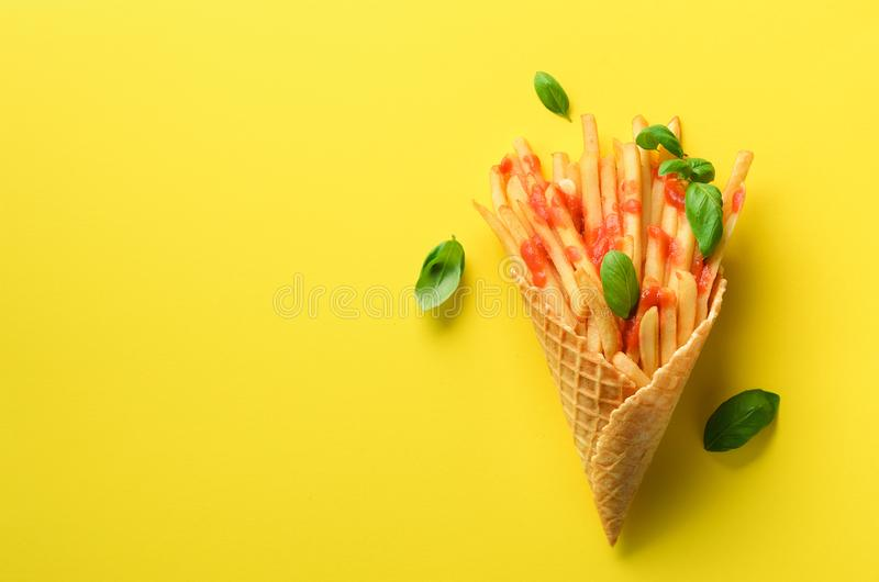 Batatas fritadas em cones do waffle no fundo amarelo As batatas fritas salgados quentes com molho, manjericão saem Fast food, suc imagens de stock royalty free