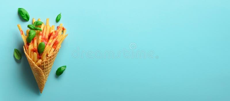 Batatas fritadas em cones do waffle no fundo azul Batatas fritas salgados quentes com molho bandeira Fast food, comida lixo, diet imagem de stock royalty free
