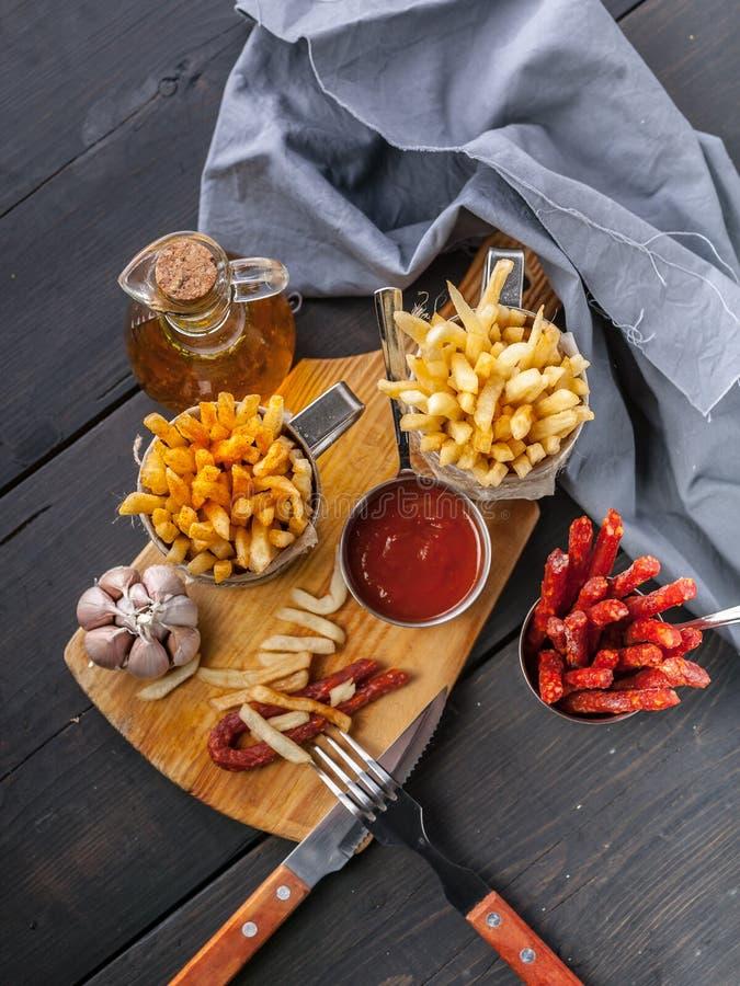 Batatas fritas caseiros, cebolas, alho, salsichas fumados, forquilha e colher na tabela de madeira escura Vista superior imagens de stock royalty free