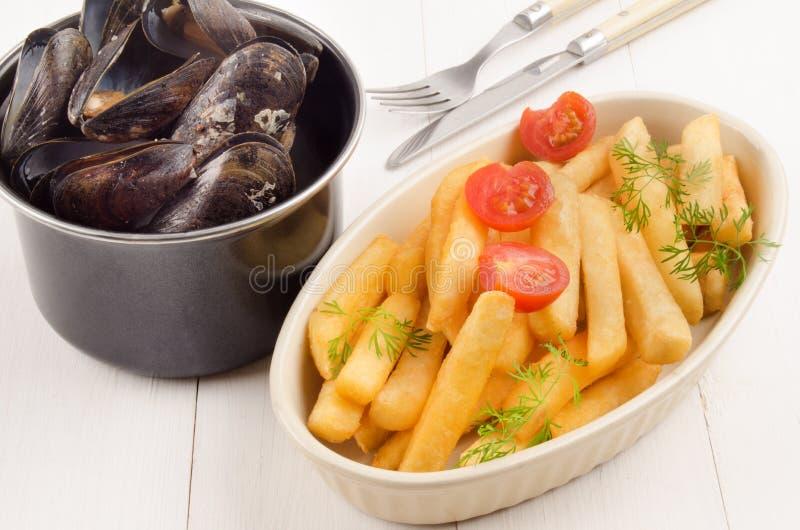 Batatas fritas com tomate e mexilhão em um potenciômetro fotos de stock