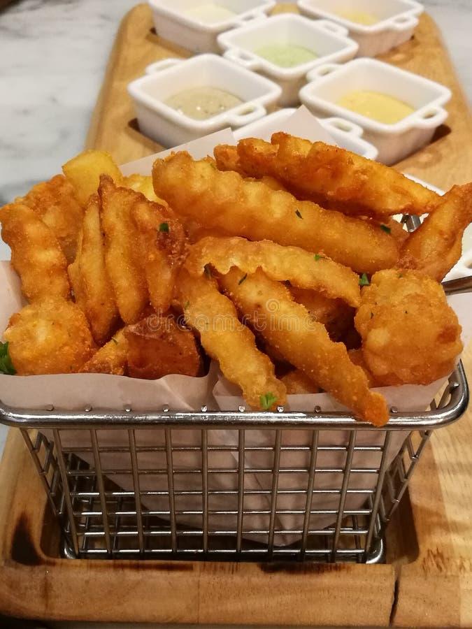 Batatas fritas douradas que servem na cesta com 8 molhos de mergulho, ketchup e Mayo, alimento do estilista, alimento da fusão foto de stock royalty free