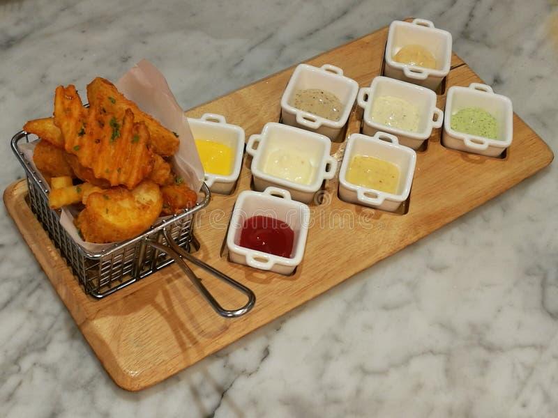 Batatas fritas douradas que servem na cesta com 8 molhos de mergulho, ketchup e Mayo, alimento do estilista, alimento da fusão fotos de stock