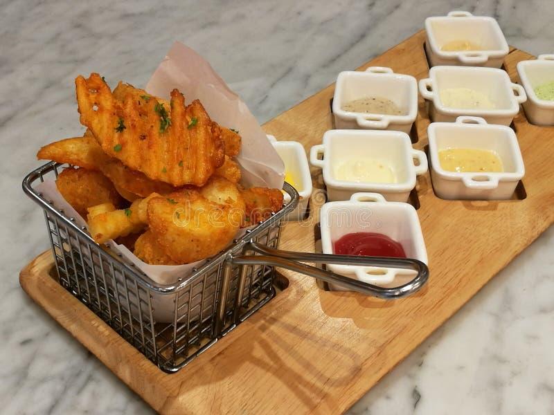 Batatas fritas douradas que servem na cesta com 8 molhos de mergulho, ketchup e Mayo, alimento do estilista, alimento da fusão foto de stock
