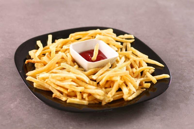 Batatas fritas na placa que está a tabela de madeira imagem de stock royalty free