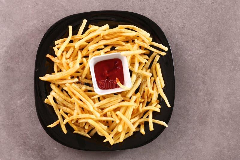 Batatas fritas na placa que está a tabela de madeira fotografia de stock