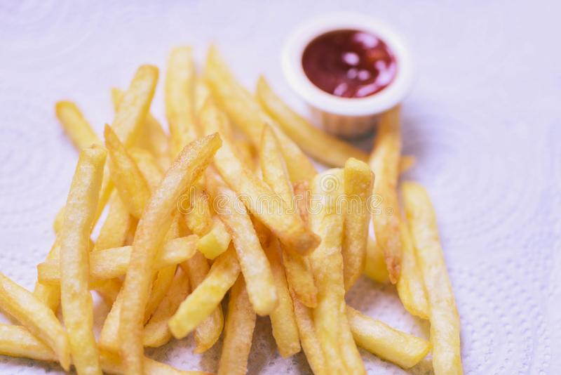 Batatas fritas no Livro Branco com ketchup no jantar imagem de stock royalty free