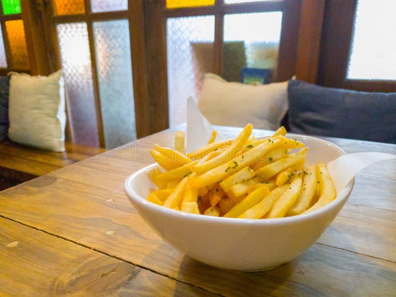 Batatas fritas ou microplaqueta de batata na tabela de madeira fotos de stock