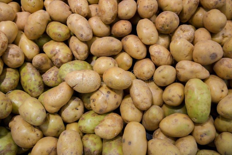 Batatas novas orgânicas frescas vendidas no mercado Teste padrão do alimento dos vegetais crus das batatas no mercado A batata or fotografia de stock royalty free