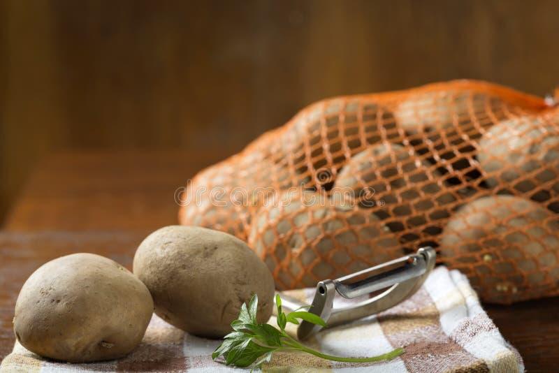 Batatas que são fora do saco da juta pronto para ser descascado imagens de stock