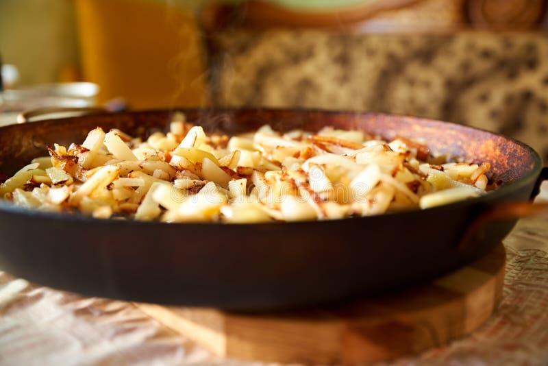 Batatas quentes fritadas douradas torradas cozidas das batatas fritas que fritam e pronto para ser comido Batatas fritadas na ban fotografia de stock