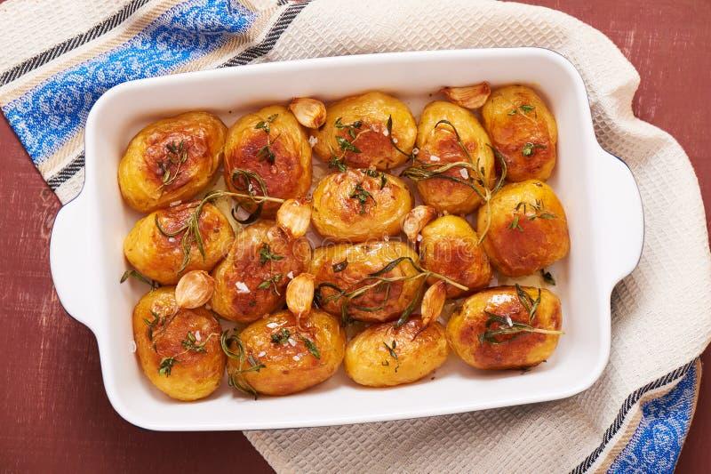 Batatas Roasted com alho, tomilho e alecrins no prato cerâmico do cozimento imagem de stock