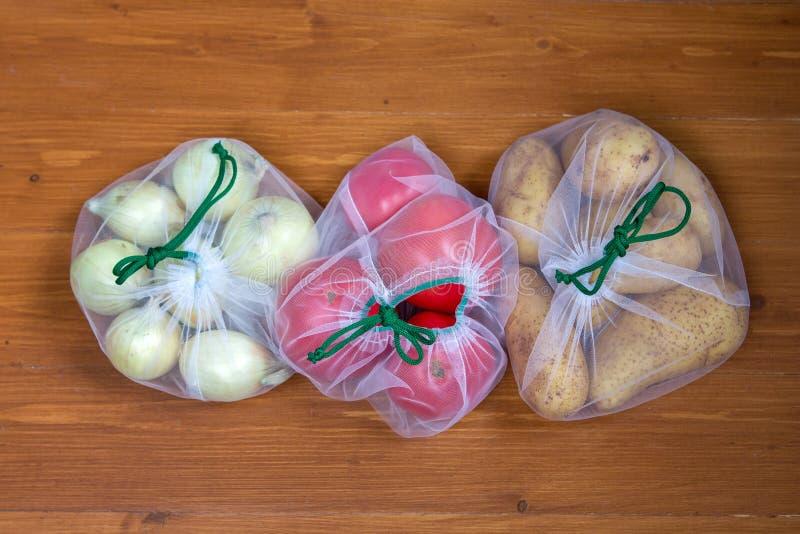 Batatas, tomates, cebolas no empacotamento ecológico Sacos reusáveis para vegetais e frutos Compra na loja Eco-amig?vel fotos de stock