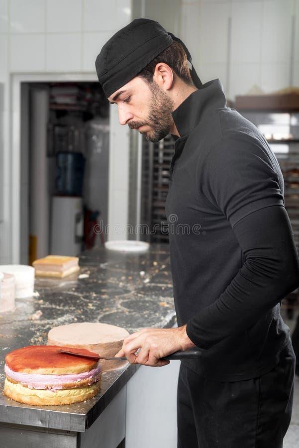Όμορφος επαγγελματικός ζαχαροπλάστης που κάνει μια batch εύγευστου κέικ στο κατάστημα ζύμης στοκ φωτογραφία με δικαίωμα ελεύθερης χρήσης