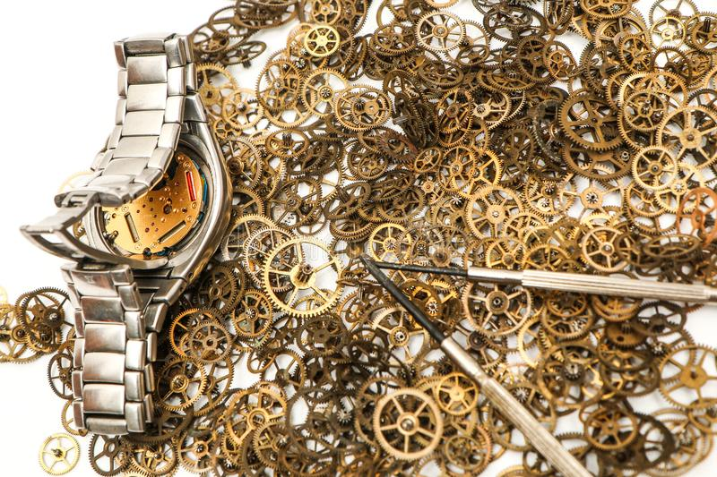 Batch of cogwheels with an analog wrist watch. A picture of a small batch of cogwheels with an analog wrist watch on a white background royalty free stock photos