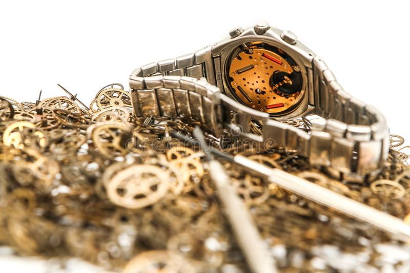 Batch of cogwheels with an analog wrist watch. A picture of a small batch of cogwheels with an analog wrist watch on a white background royalty free stock images