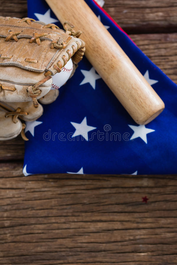 Bate de béisbol y guantes en una bandera americana imagen de archivo libre de regalías