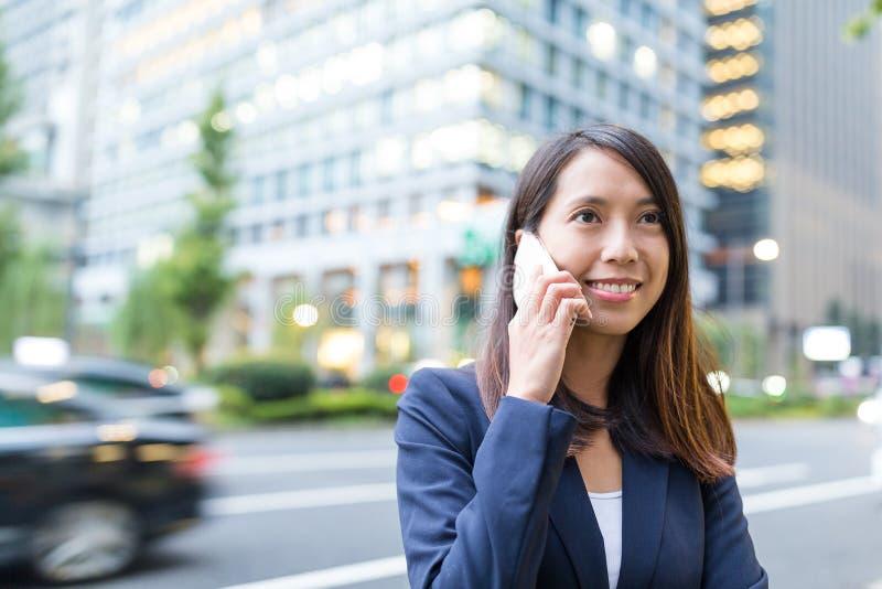 Bate-papo da mulher de negócios no telefone celular na cidade do Tóquio foto de stock royalty free