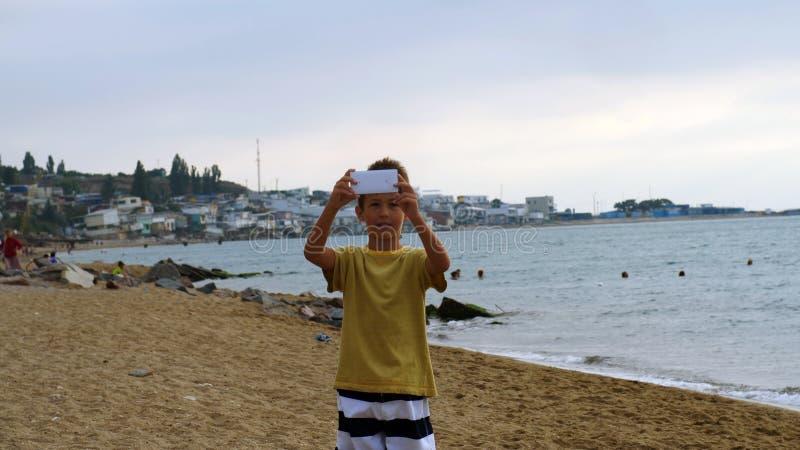 Bate-papos video do menino no telefone esperto na praia na noite Usando um dispositivo handheld portátil em férias de verão falar imagens de stock royalty free