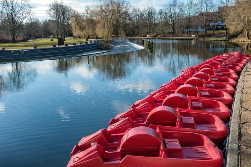 Bateas rojas del pedal en el río de Odense, Dinamarca imagenes de archivo