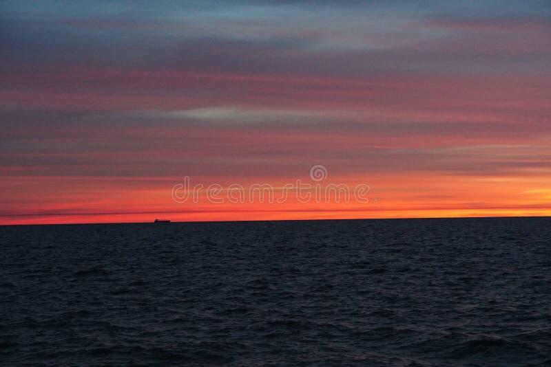 Bateau à l'horizon sur la rivière large au lever de soleil photo libre de droits