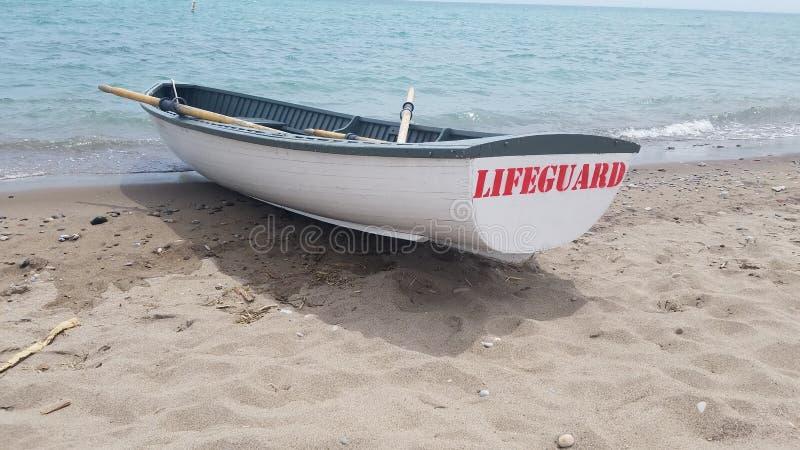 Bateau à rames de maître nageur sur la côte images stock