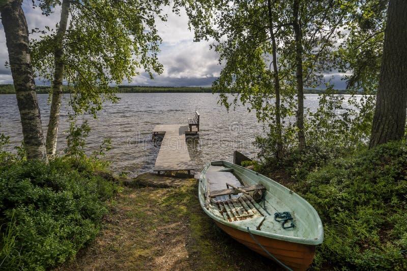 Bateau à rames et banc en bois dans Rantasalmi, lacs secteur, Finlande photo stock