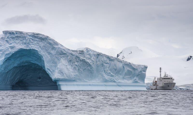 Bateau à un milieu des glaciers massifs outre de la côte de la péninsule antarctique images libres de droits