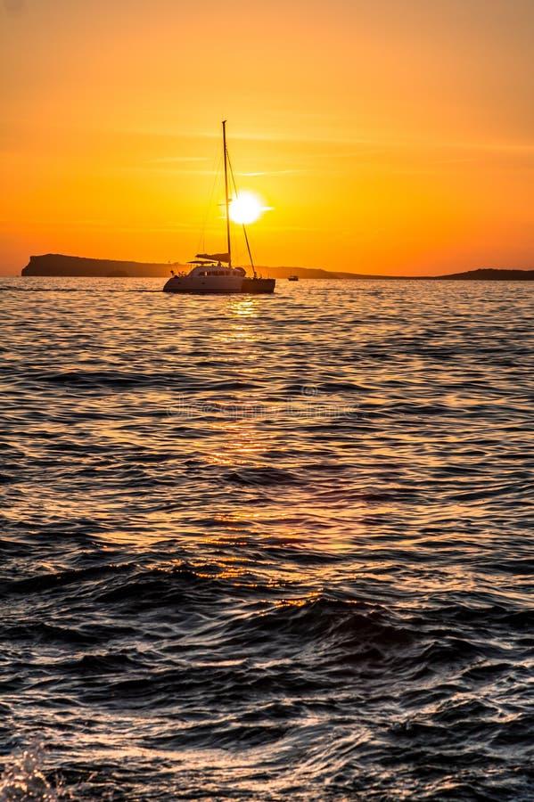 Bateau à voile contre le coucher du soleil image libre de droits