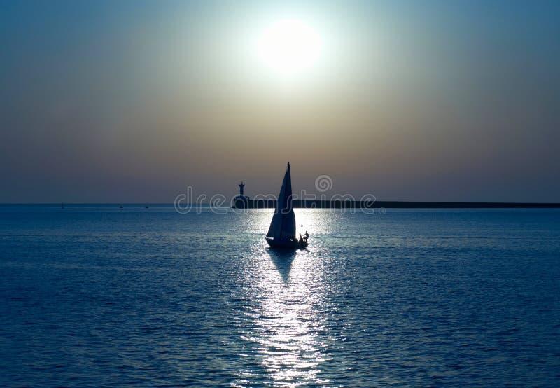 Bateau à voile contre le coucher du soleil photographie stock libre de droits