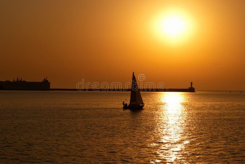 Bateau à voile contre le coucher du soleil photo libre de droits