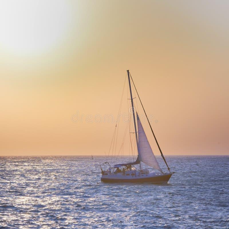 Bateau à voile contre le coucher du soleil de mer photo stock