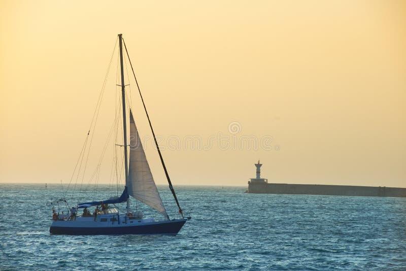 Bateau à voile contre le coucher du soleil de mer photographie stock libre de droits