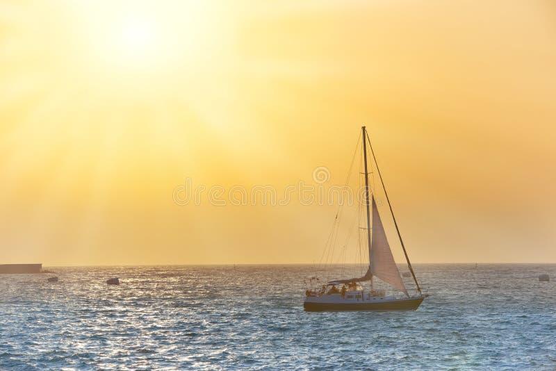 Bateau à voile contre le coucher du soleil de mer photos stock
