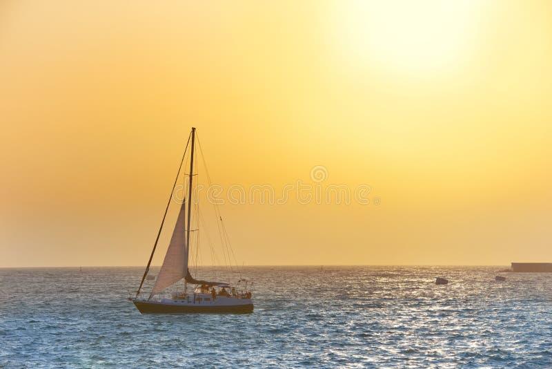 Bateau à voile contre le coucher du soleil de mer image stock