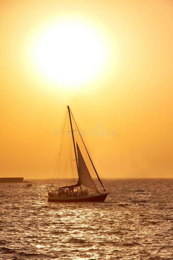 Bateau à voile contre le coucher du soleil de mer images libres de droits