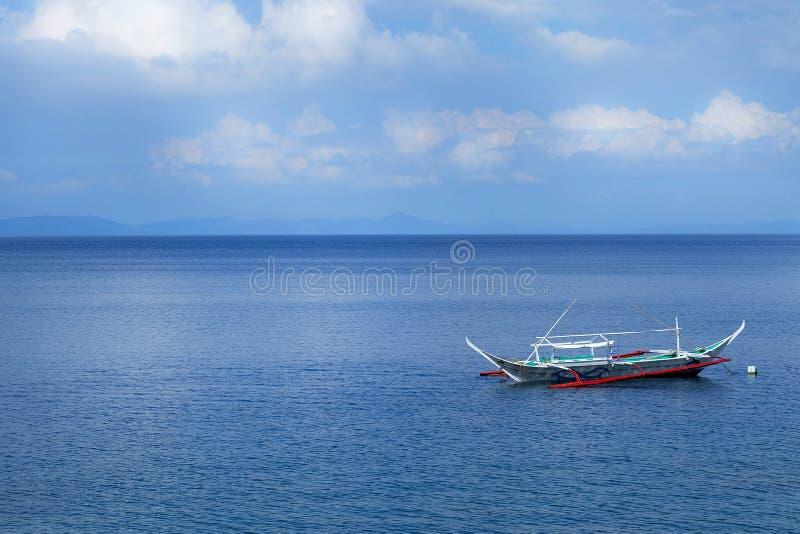 Bateau à voile dans l'océan bleu d'Anilao photo stock