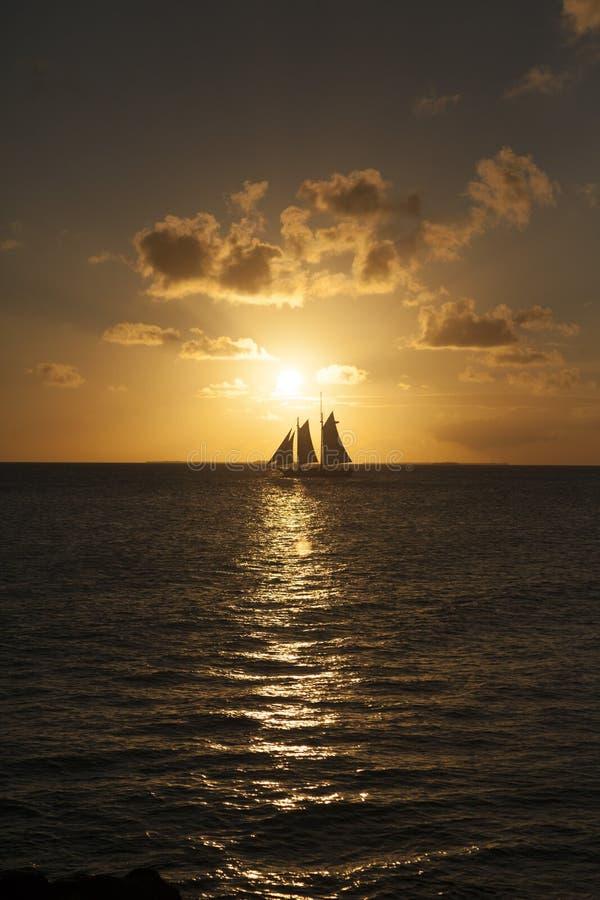Bateau à voile dans le coucher du soleil image libre de droits