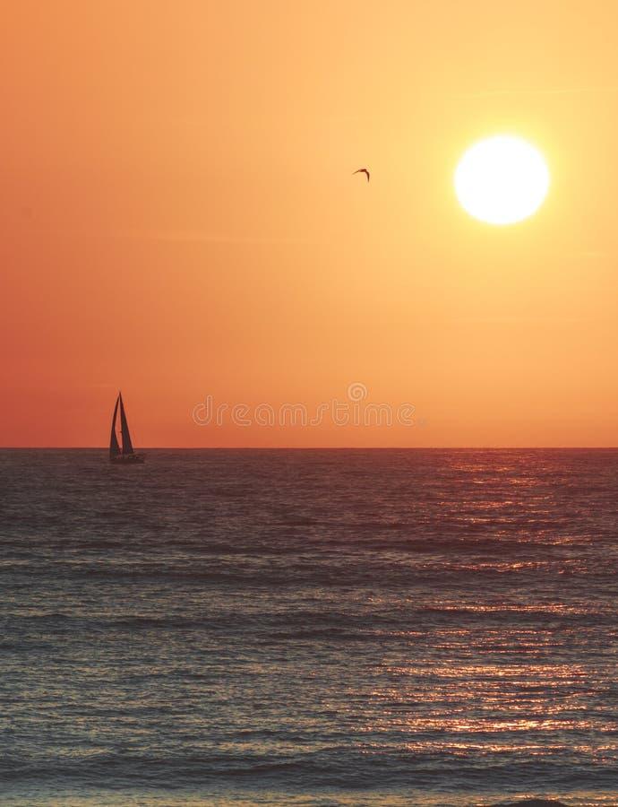 Bateau à voile simple dans l'océan pacifique avec une orange d'or et un coucher du soleil jaune dans la distance Le soleil jaune  photos libres de droits