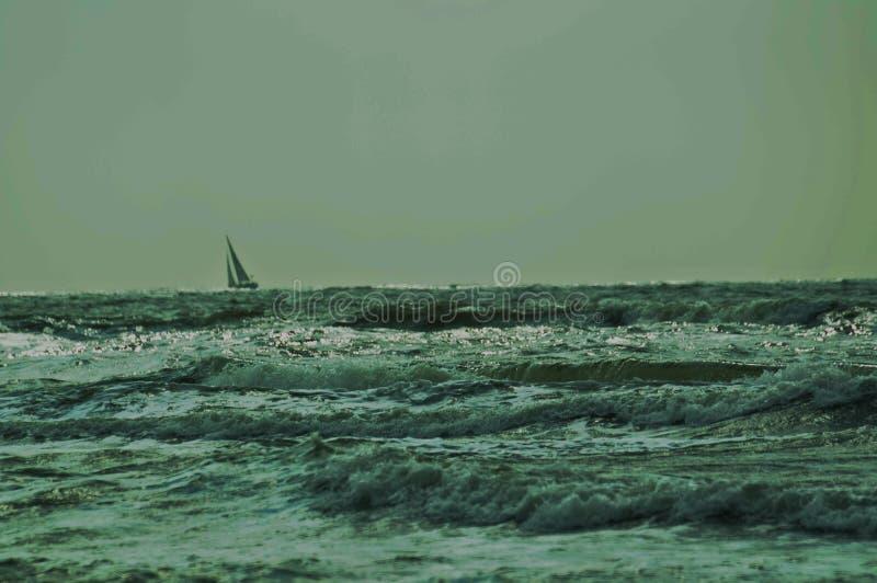 Bateau à voile sur des vagues image stock