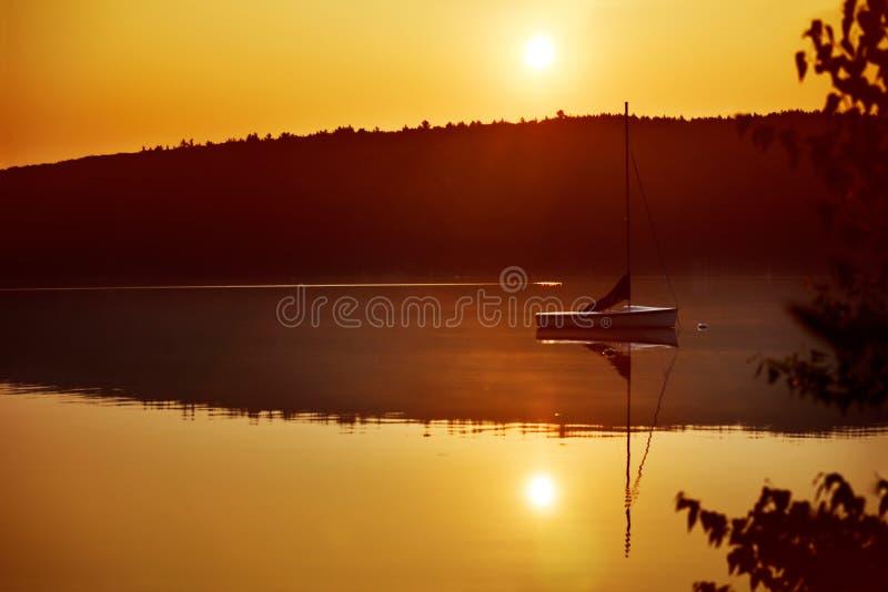 Bateau à voiles au lever de soleil image stock
