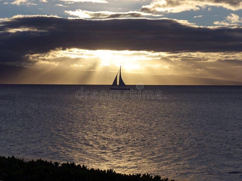 Bateau à voiles glissant au coucher du soleil photo stock